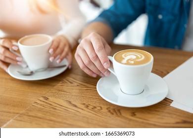 熱いコーヒーを持つ男女の接写