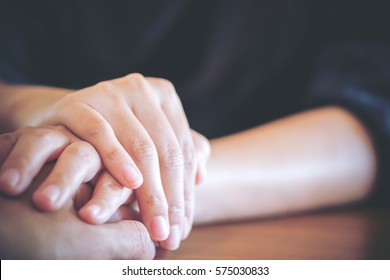 A man and a woman holding each other hands with feeling love and warmness
