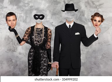 Man and woman holding each other's face mask
