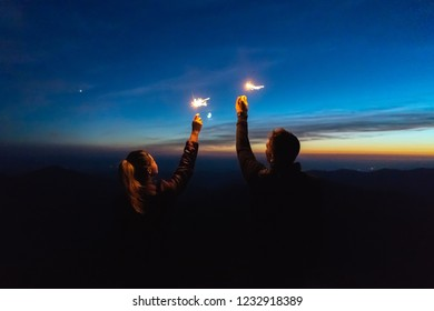 The man and a woman holding firework sticks. evening night time