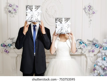 Man and woman holding gifts at face level. Funny bride and groom with gifts in their hands. Face is covered with gift box in silver paper. Christmas festive mood concept wedding day, original wedding