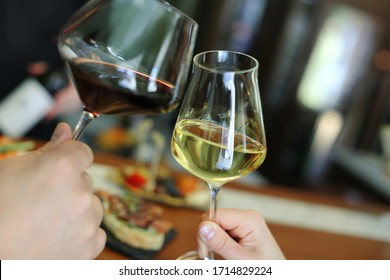 Man and woman are holding glasses with wine. Red and white wine in glasses. Date concept. Dinner for two. Selective focus. Celebration.