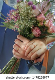 Man and woman holding hand with engagement rings on hands with pink flower bouquet at registration of marriage