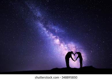 Man and woman holding hands in heart shape on the background of the Milky Way