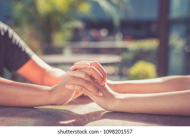 Man and woman holding hands together at restaurant cafe,filter color effect, closeup