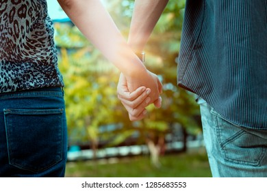 Man and woman holding hands walking in park with sunset scene.