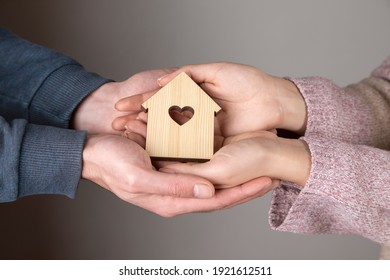 man and woman holding house model with heart window