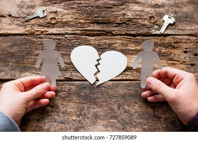 man and woman holding paper silhouettes against a broken heart concept divorce
