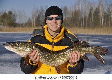 man and woman holding a pike on the ice. winter fishing