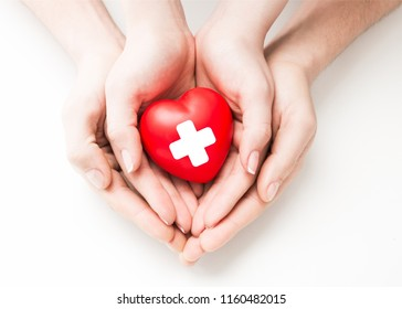 Man and woman holding red heart in hands isolated