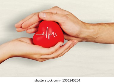 Man and woman holding red heart in