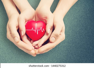 Man and woman holding red heart in hands on blurred background