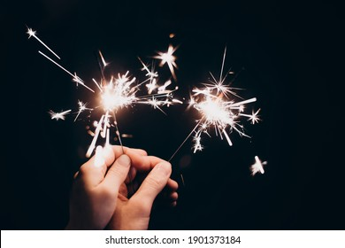 A man and a woman are holding sparklers in their hands on a black background, hands close-up, shallow depth of field