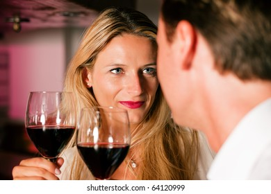 Man and woman in a hotel bar in the evening having glasses of red wine and a little flirt