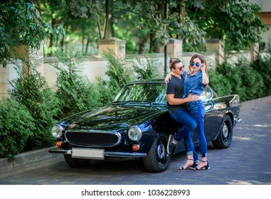 Man and woman hug each other with passion posing before a black sport retro car