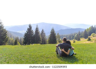 man and woman hugging and enjoying view on mountains and pine forest