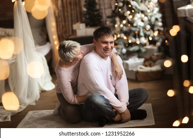 man and a woman are hugging together background of New Year tree in real interior, the parents are together in bedroom decorated for Christmas
