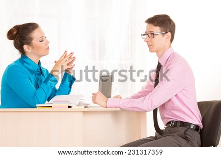 Man and woman - a job interview or business meeting. Male student came to the office to get a job. HR Manager conducts the first interview. Agree on. Discuss the possibilities of business cooperation.