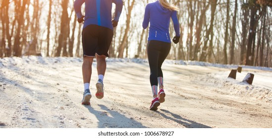 Man and woman jogging in nature, back view