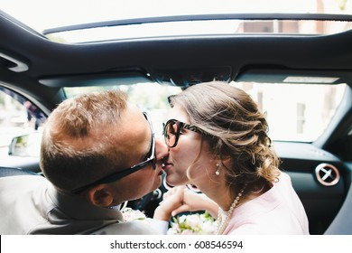Man and woman kiss each other sitting on front seat in the Mercedes