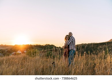 man and woman are kissing at sunset