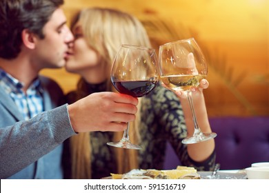 A man and woman kissing while clinking glasses of red and white wine sitting at the table with plate of oysters surrounded by yellow sun light during a romantic dinner