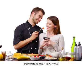 A man with a woman in the kitchen, a girl with a glass of wine, a man feeding a girl with strawberries.