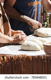 man and woman kneading bread dough balls at a market stall