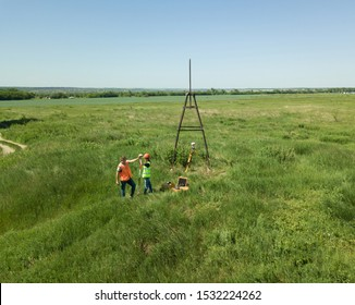 Man and Woman land surveyors a construction site. Young engineers surveyor in helmets give each other five.