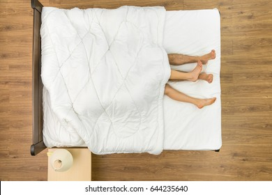 The man and woman lay under duvet. View from above