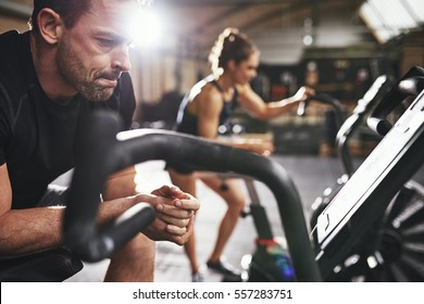 Man and woman leaning on cycling machines taking rest after riding workout in lighr spacious gym.
