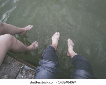 Man and woman legs dangling in the river