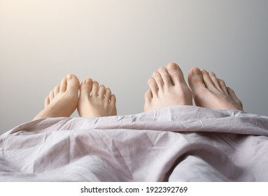 Man and woman legs on bed. Couples feet in bed, close up. Good morning.