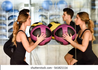 Man and Woman lifting fitballs in the gym. Young people wearing sportswear clothes in front of a mirror.