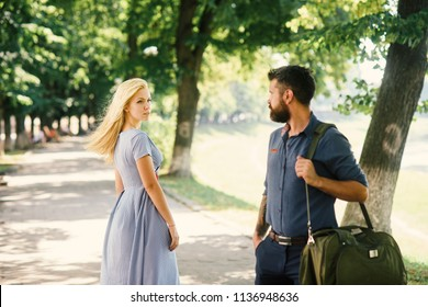 Man and woman likes each other. Man with beard and blonde girl stopped to get acquainted. Casual encounter, meet on sunny summer day, nature background, defocused. Love at first sight concept.