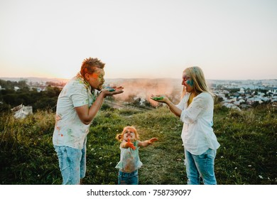 Man and woman look funny playing with colorful paints and powder with their daughter
