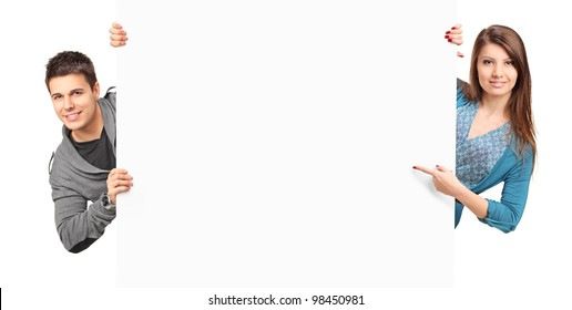 A man and woman looking behind white panel isolated on white background