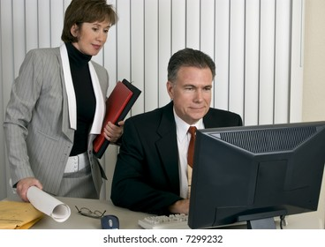 A man and a woman looking at a computer screen with pleased expressions on their faces.