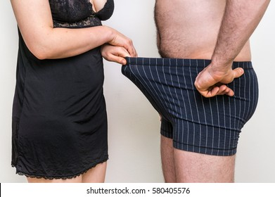 Man and woman looking down into underwear - impotence concept