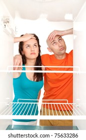 Man and woman looking into an empty refrigerator.