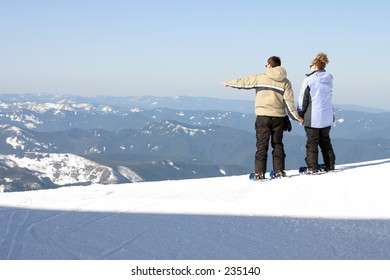 man and woman looking out from atop a mountain