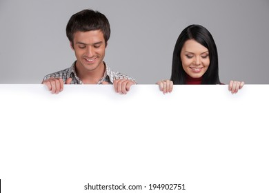 man and woman looking at white panel. Young Happy Couple Holding Placard Over White Background