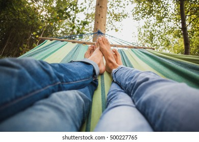 man and woman in love lying in hammock embracing, legs close-up details, romance, autumn vacation, denim outfit, blue jeans, nature, forest, barefoot
