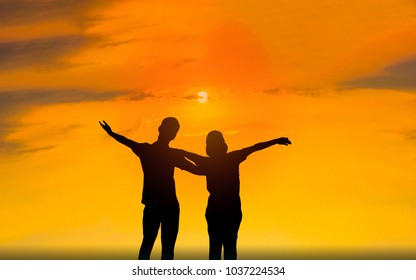 Man and woman in love. They are standing and see the sun set. Woman wearing a hatand man Man hugging woman.Photo concept Silhouette and love.