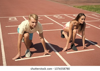 Man and woman low start position running surface stadium. Running competition or gender race. Faster sportsman achieve victory. Sport challenge for couples. Everyone has chance. Equal forces concept.
