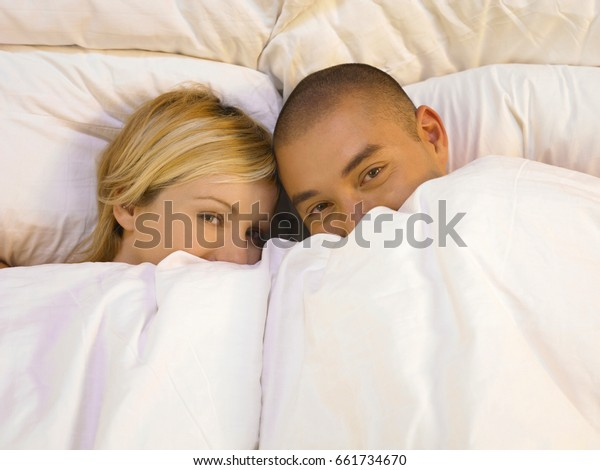 Man and woman lying in bed, holding blanket over their faces
