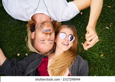 Man and woman lying on green grass in park and passing marijuana joint