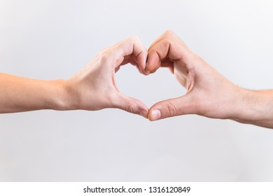 Man and woman make heart symbol on a white background. Love concept.