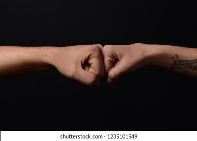 Man and woman making fist bump gesture on dark background