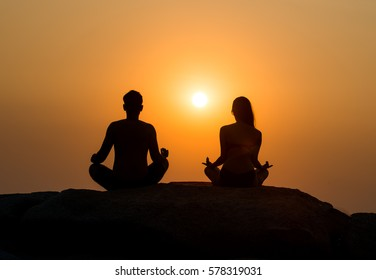 man and woman meditating at sunset sitting on a rock , Yoga meditation - silhouettes of people at sunset. Silhouette of a couple practicing yoga at sunset sitting on the lock